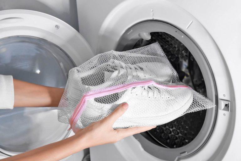 Tenisky perte v pračce vložené v ochranném sáčku.